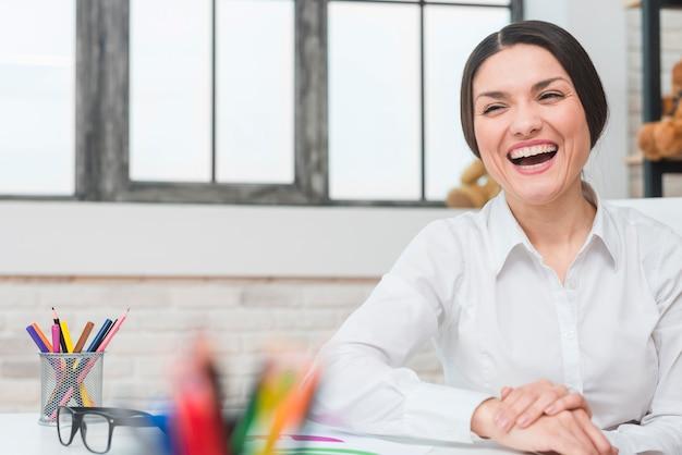 オフィスで笑って幸せな女性心理学者の肖像画 無料写真