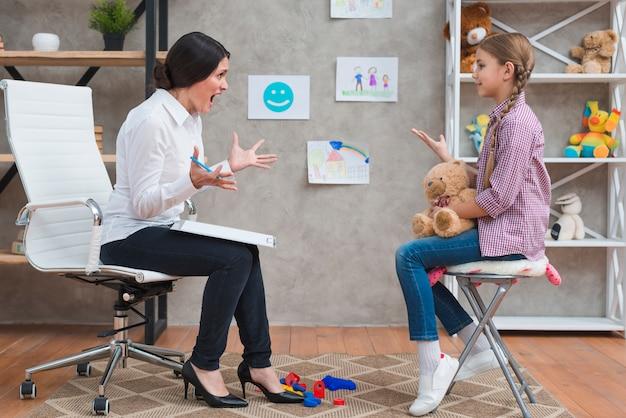 テディベアと座っている女の子に叫んで怒っている若い女性心理学者 無料写真