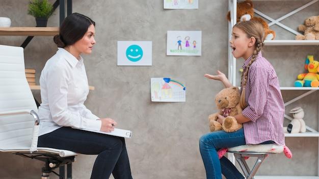 Подавленная девушка сидит перед женщиной-психологом и разговаривает с ней Бесплатные Фотографии