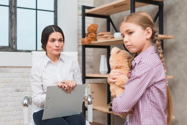 テディベアを手で押し悲しい少女とのセラピーセッションを持つ女性心理学者 無料写真