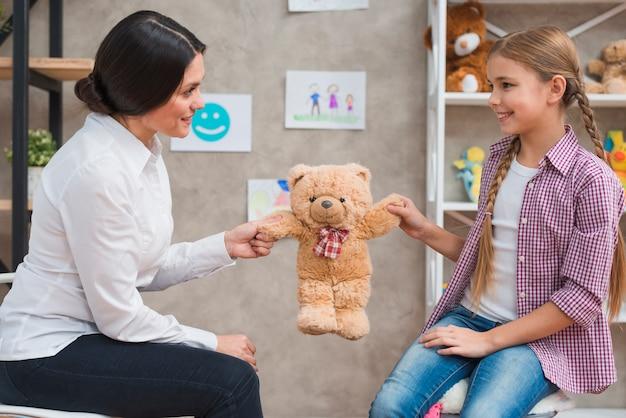 Крупный план женского психолога и улыбающаяся девочка держит в руках ребёнка Бесплатные Фотографии