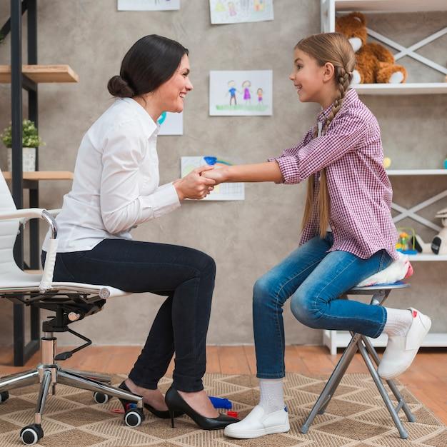 セラピーセッションで女の子の手を繋いでいるフレンドリーな女性心理学者 無料写真