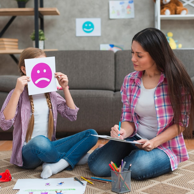 悲しい感情カードで彼女の顔を覆っている女の子を見てメモを取って女性心理学者 無料写真