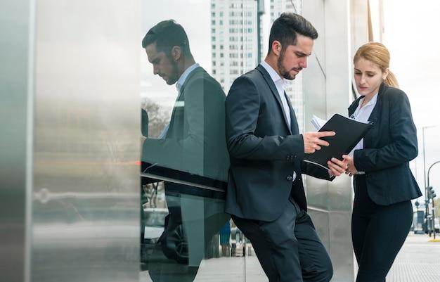 ビジネスマンやビジネスウーマン、オフィスの外に立っている書類を見て 無料写真