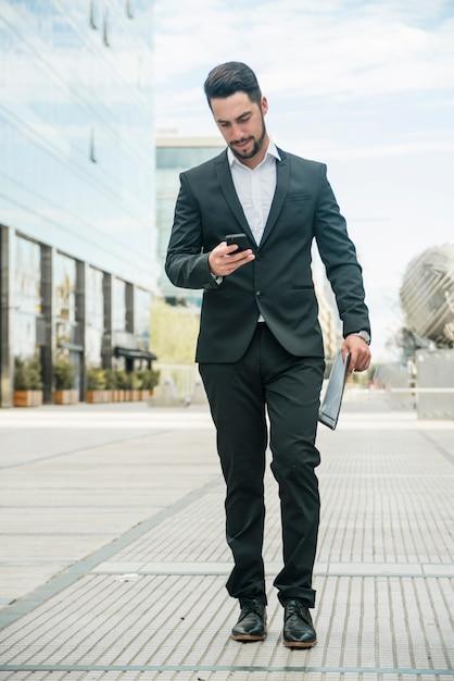キャンパス内の舗装の上を歩きながら彼の電話を使用して青年実業家 無料写真