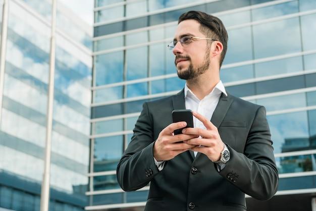 携帯電話を保持している事務所ビルの前に立っている青年実業家 無料写真