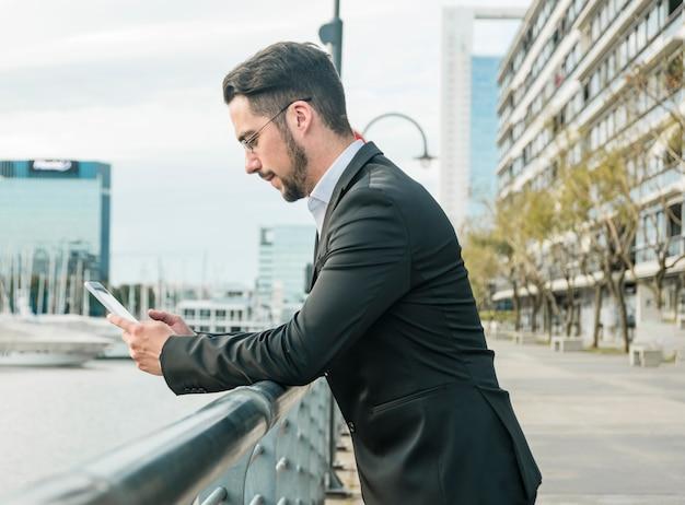 スマートフォンを使用して手すりの近くに立っている青年実業家の側面図 無料写真