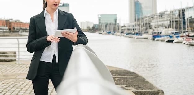 Крупный план молодой предприниматель, опираясь на перила возле гавани, с помощью мобильного телефона Бесплатные Фотографии