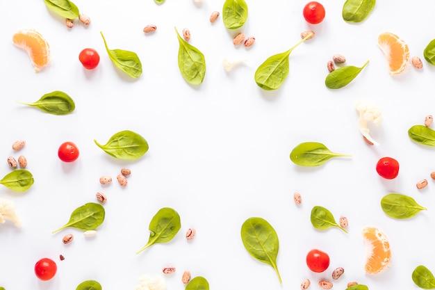 ピント豆。白い背景に配置された野菜とオレンジのスライス 無料写真