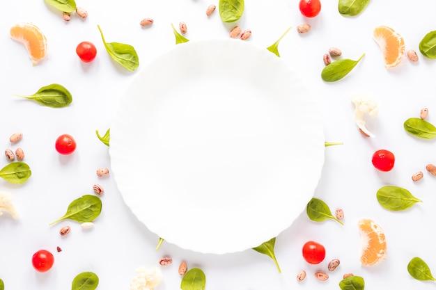 ピント豆に囲まれた空のプレート。野菜とオレンジのスライスを白の背景に配置 無料写真