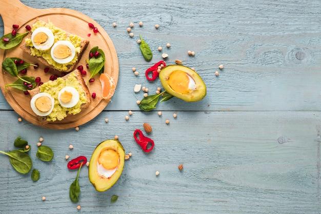 まな板の上のゆで卵とトーストのパンとアボカドで焼き有機卵 無料写真