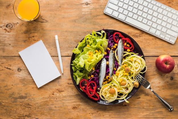 プレートに配置された生の魚のヘルシーサラダ。ジュース;林檎;キーボードとメモ帳。木製の机の上のペン 無料写真