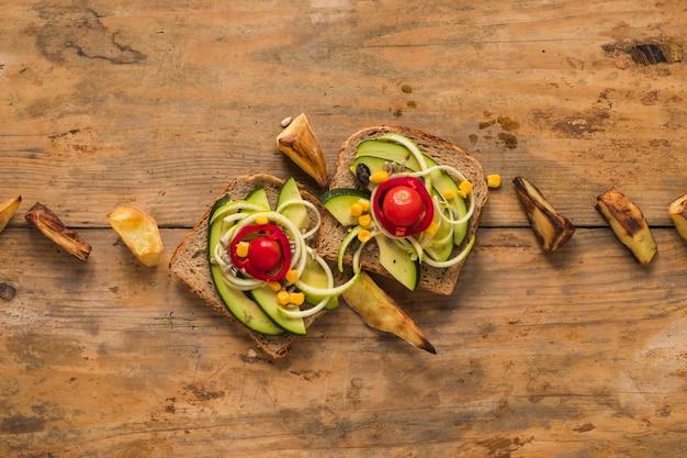 木製のテーブルにローストポテトスライスと野菜のサンドイッチのトップビュー 無料写真
