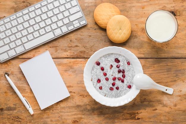 チアシードプディング;クッキー;スムージーミルク;メモ帳木製の背景にペンとワイヤレスコンピューターのキーボード 無料写真