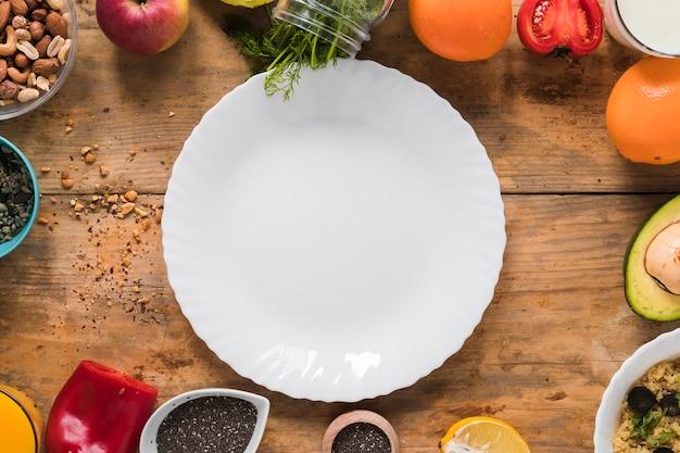 ドライフルーツに囲まれた空の白いプレート。野菜;木製のテーブルの上の果物 無料写真