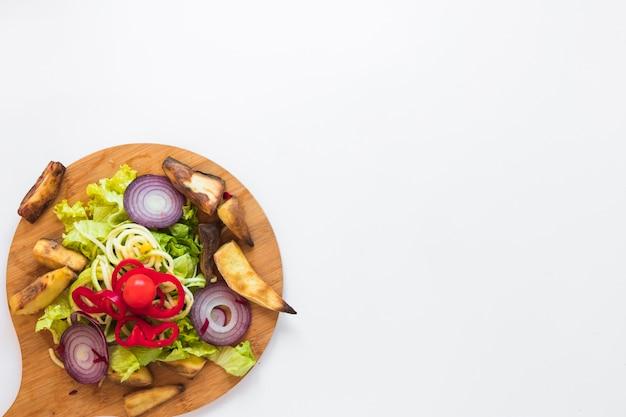 みじん切り野菜と木製のまな板の上のローストポテト 無料写真
