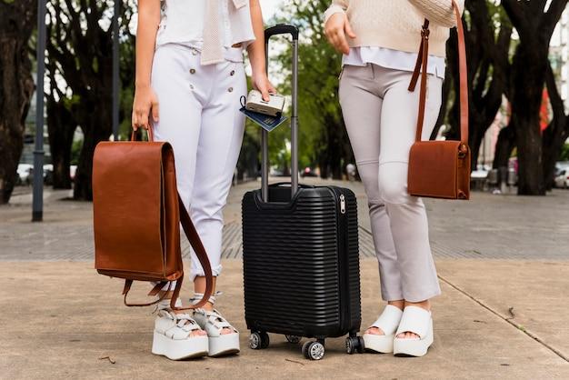 Низкая часть двух молодых женщин, стоящих с черным чемоданом и их кожаными сумками Бесплатные Фотографии