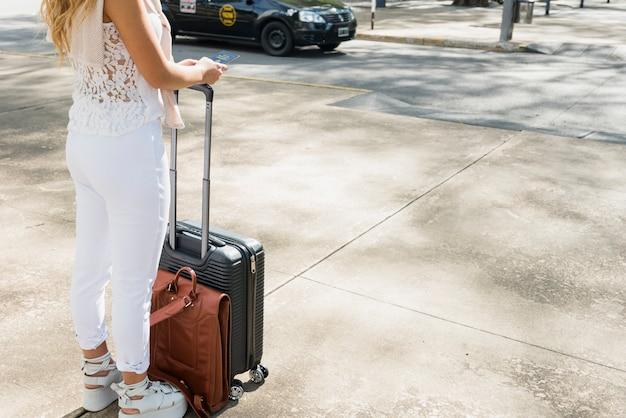 荷物旅行バッグとパスポートを保持している道路上に立っている女性観光客のクローズアップ 無料写真