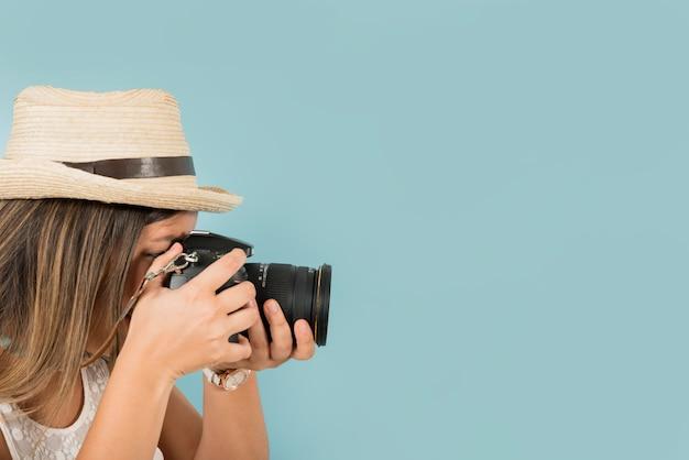 女性観光客が青い背景にプロのカメラで写真を撮る 無料写真
