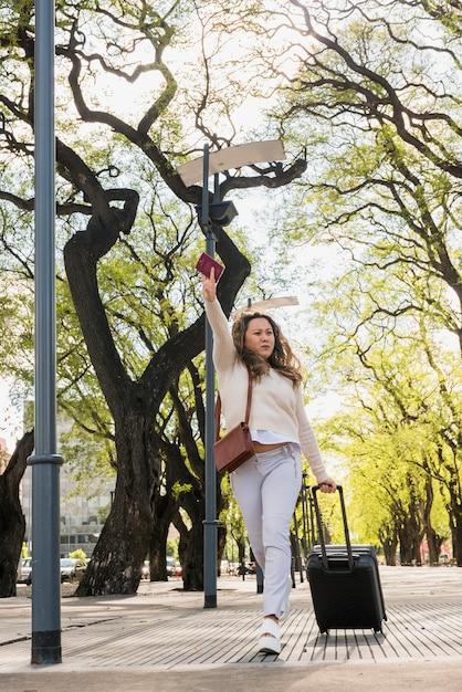 Молодая женщина с багажом, паспорт спешит за оклик такси Бесплатные Фотографии