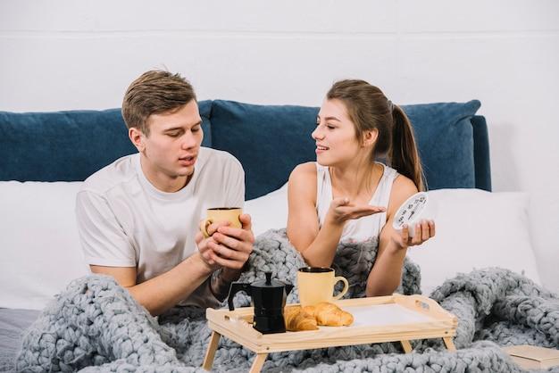 不満の女性がベッドの中で時計を表示 無料写真