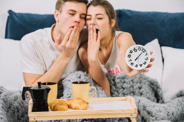 食品トレイ付きベッドであくびカップル 無料写真