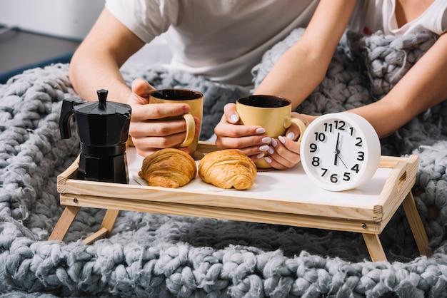 柔らかいベッドでコーヒーを飲むカップル 無料写真