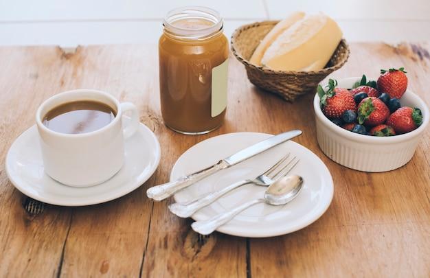 コーヒーカップ;カトラリーのセット。ジャムメイソンジャー。パンとベリーの木製のテーブル 無料写真