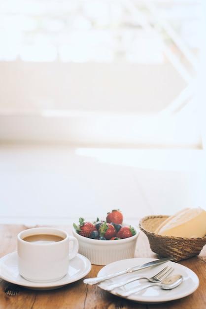 新鮮な果実と木製の背景の皿にカトラリー一杯のコーヒー 無料写真