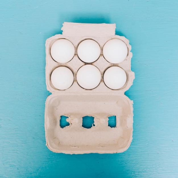 青色の背景にカートンの卵の俯瞰 無料写真