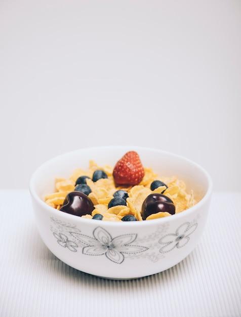 白い背景の上にボウルに果実とコーンフレークシリアル 無料写真