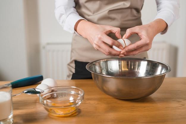 木製のテーブルのミキシングボウルに卵を壊す女性の手のクローズアップ 無料写真
