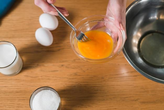 ガラスのボウルに卵黄とフォークを混合する女性の手のクローズアップ 無料写真
