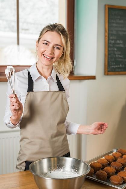 コーヒーショップで泡立て器でクリームを保持している若い女性を笑顔 無料写真