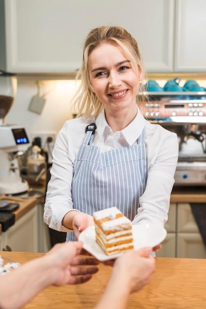 コーヒーショップで女性客にペストリーケーキを提供する若い女性の笑みを浮かべてください。 無料写真