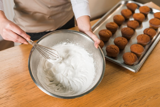 女性のオーバーヘッドビューは、木製のテーブルの上にボウルにクリームを作るための泡立て器で卵白をホイップクリーム 無料写真