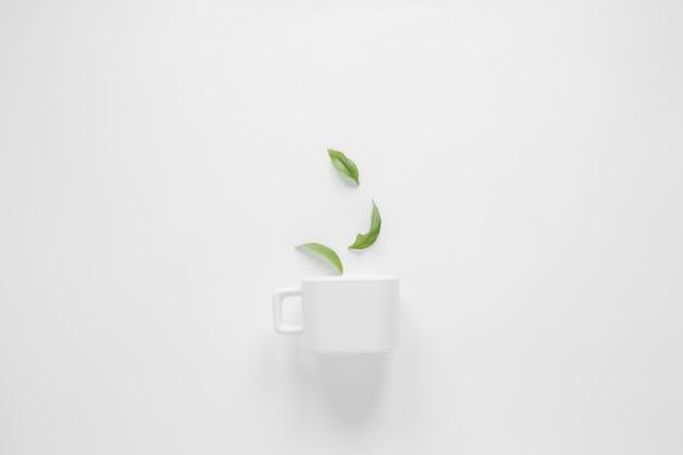 コーヒーの葉と白い背景の上の白いカップ 無料写真