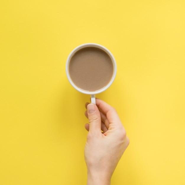 黄色の背景に一杯のコーヒーを持っている人の手のクローズアップ 無料写真