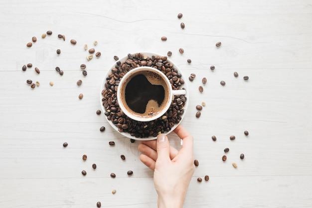 コーヒー豆と一杯のコーヒーとソーサーを持っている人の手の上から見た図 無料写真