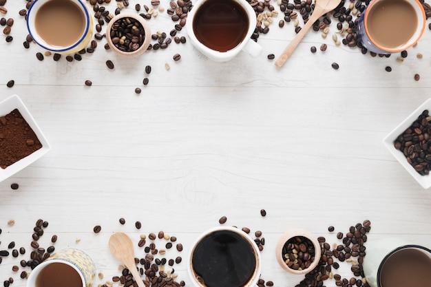 さまざまな種類のコーヒー。生コーヒー豆。コーヒー豆の焙煎白いテーブルの上に配置されたコーヒーの粉 無料写真