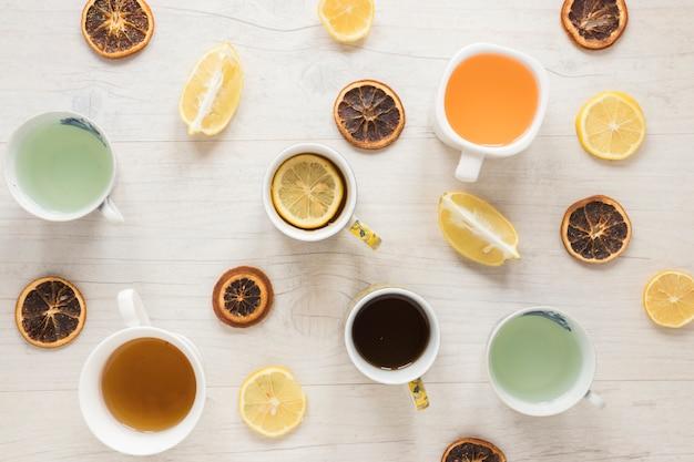 セラミックカップに入っている様々な種類のお茶。木製の背景にレモンとドライグレープフルーツのスライス 無料写真