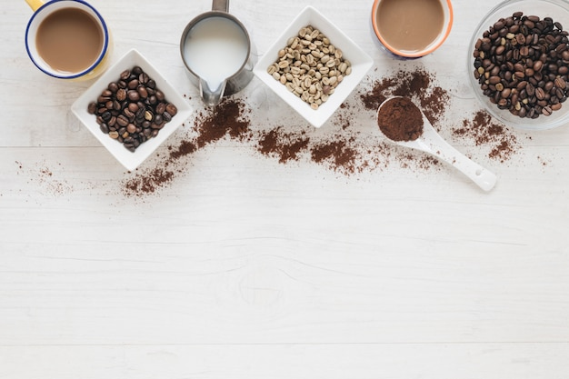 Вид сверху сырых и жареных кофейных зерен с чашкой кофе на деревянный стол Бесплатные Фотографии