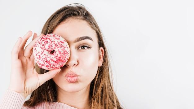 唇をふくれっ面と白い背景で隔離のドーナツで目を覆っている若い女性のクローズアップの肖像画 無料写真