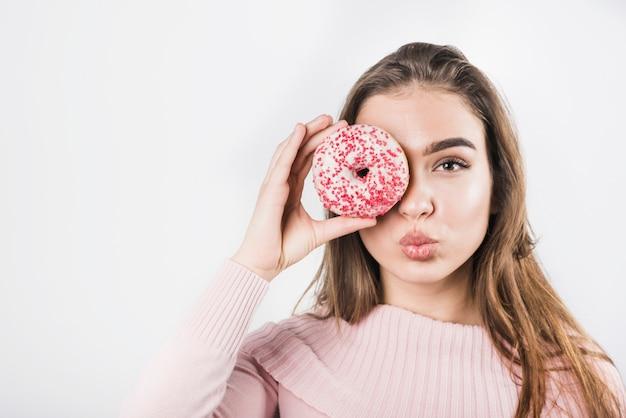 白い背景の上にドーナツと彼女の目を覆っている彼女の唇をふくれっ面の若い女性 無料写真