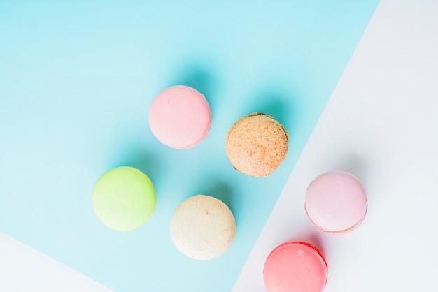 Вид сверху красочные миндальное печенье на синем и белом фоне двойной Бесплатные Фотографии