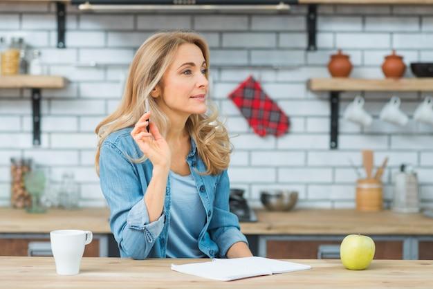 本と手でペンを持つ思いやりのある金髪の若い女性。木製のテーブルの上のリンゴと白のカップ 無料写真