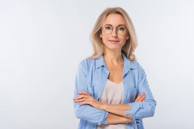 Уверенно блондинка молодая женщина со скрещенными руками, стоя на белом фоне Бесплатные Фотографии