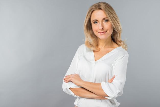 灰色の背景に対して立っている彼女の組んだ腕を持つ金髪の若い女性の笑みを浮かべてください。 無料写真