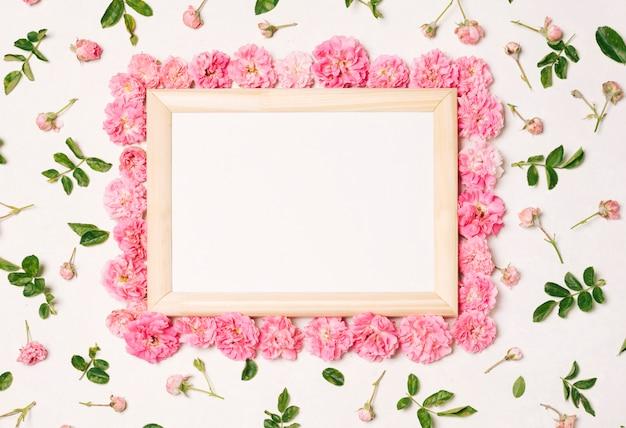 ピンクの花と緑の葉のセットの間のフォトフレーム 無料写真
