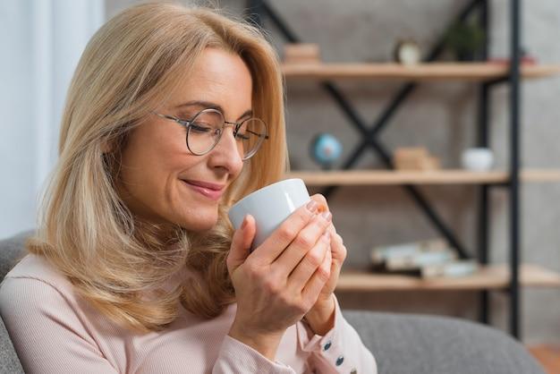 彼女の目を閉じてコーヒーの香りを取っている女性のクローズアップ 無料写真